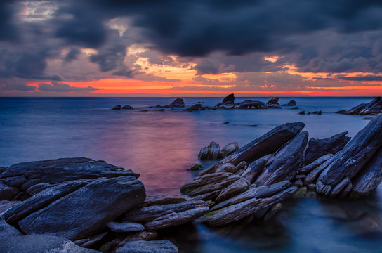 Sunrise over lake Malawi with rock formation in the foreground under cloudy dramatic sky