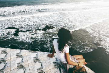 Young hipster traveler girl sitting on storm sea view with rocks