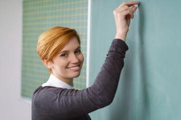 lächelnde junge lehrerin schreibt an die tafel