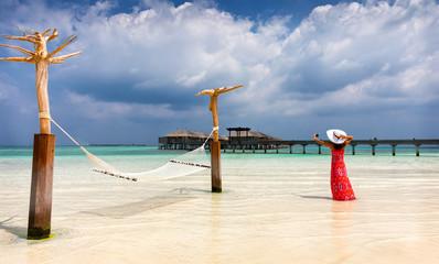 Elegante Frau im roten Kleid fotografiert die Landschaft auf den Malediven
