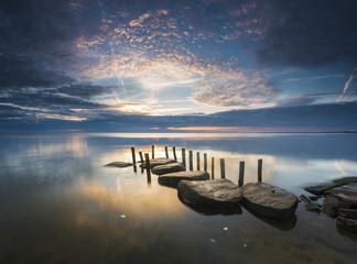 sea landscape at sunrise, boulders on the sea shore