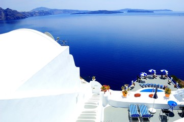 Piece of Mediterranean cruise On Santorini island, Greece. The view from the hotel balcony on the lower terrace and the shore of the Aegean sea. The system of the Cycladic Islands