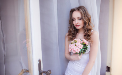 Elegant bride in white lingerie holds pink bouquet standing before the window