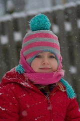 adorable school age girl smiling wearing winter hat scarf and jacket in snow