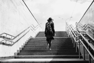 black and white art photography monochrome, girl in a hat rises from the underpass. A woman comes out of the subway. Man climbs the stairs.