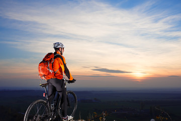 Sun rises behind man getting ready to ride his road bike on lonely paved highway during summer. Includes copy space.