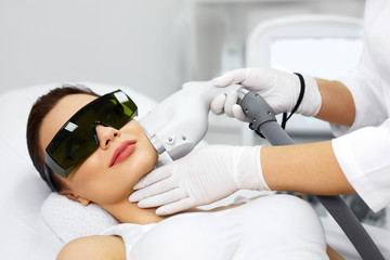 Woman Receiving Laser Hair Removal Procedure At Beauty Salon