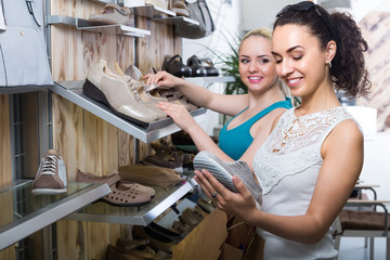 Two girls choosing shoes in the store.
