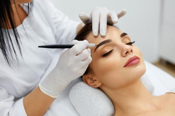 Beautician Doing Permanent Eyebrows Makeup Tattoo On Woman Face Wall mural