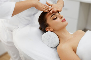 Beauty Treatment. Beautiful Woman Getting Face Head Massage