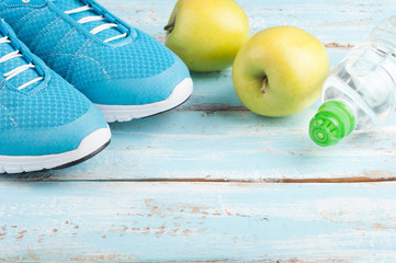 Sport shoes, apples, bottle of water on blue wooden background. Concept healthy lifestyle, healthy food, sport and diet. Sport equipment