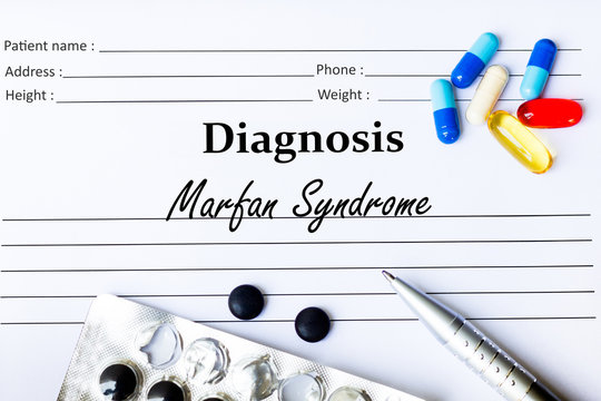 Marfan Syndrome - Diagnosis written on a piece of white paper with medication and Pills