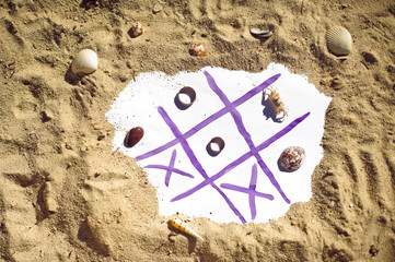 Tic Tac Toe and wedding rings on the beach. Wedding in the tropics concept