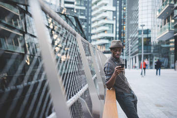 young handsome afro black man sitting on a handrail outdoorusing smart phone - technology, social network, communication concept