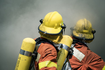 two firefighters fire fighting suround with dark smoke