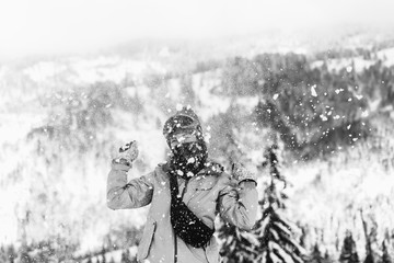 Woman in ski suit throws snow up posing on hill in the mountains