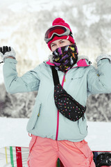 Woman in blue ski jacket raises her hands up posing on snowboard