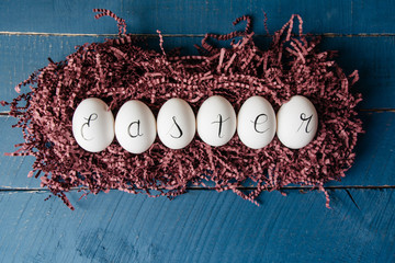 Decorative Easter eggs in a purple paper nest spelling Easter in cursive
