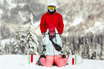 Couple in colorful ski suits poses on the hill somewhere in the mountains