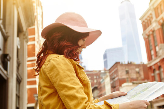 Young female tourist with long red hair looking at map on street, Manhattan, New York, USA