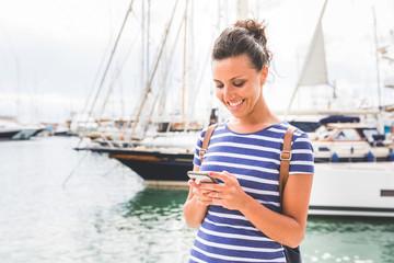 Woman using mobile phone at marina, Mallorca, Spain