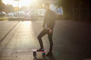 Young male skateboarder with skateboard on sunlit street