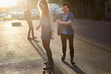 Young man pushing young female skateboarder on sunlit street