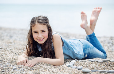 Happy little girl lying on the beach