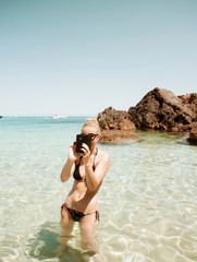 Woman in sea holding smartphone, Menorca, Spain