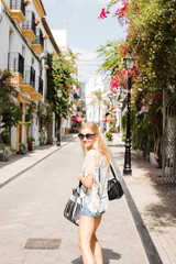 Woman in street looking at camera smiling, Marbella old town, Spain