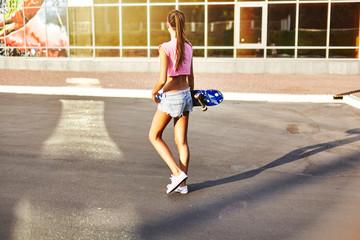 Young woman walking along road, carrying skateboard, rear view