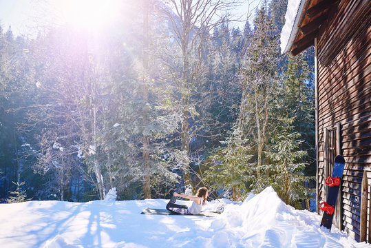 Woman practicing bow yoga pose by log cabin in snow,  Austria