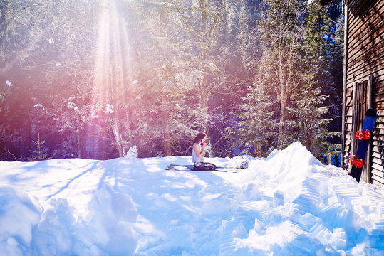 Woman practicing yoga, kneeling on yoga mat by log cabin in snow,  Austria