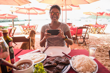 Woman taking picture of her meal with a mobile phone, Ilha Grande, Rio de Janeiro, Brazil