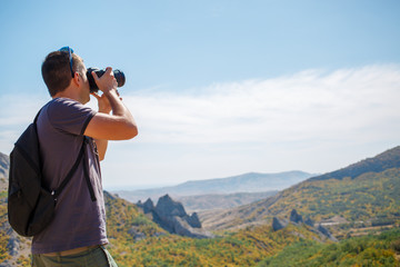 Guy photographing mountain in summer