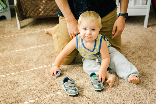 Father helping young son put on shoes