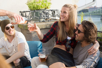 Adult friends relaxing and pouring wine at roof terrace party
