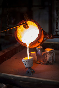 Molten bronze being poured from pot in foundry
