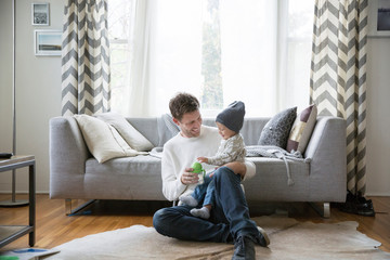 Father and young son at home, playing