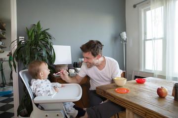 Young boy sitting in highchair, father spoon feeding him food
