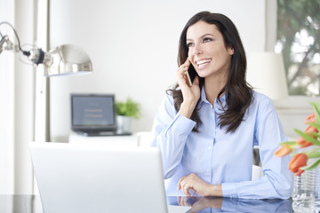 Staying connected in the office. Professional businesswoman using mobile phone while working at office
