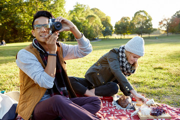 Mid adult man with girlfriend taking photographs during park picnic