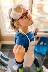 Girl doing science experiment, pulling a face and clenching fist