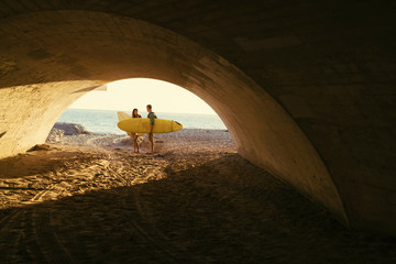 Surfing couple in underpass at Newport Beach, California, USA
