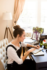 Female fashion and lifestyle blogger writing in notebook at desk