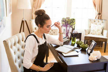 Female fashion and lifestyle blogger contemplating notebook at desk