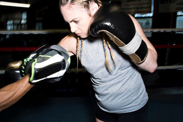 Female boxer punching her trainer's boxing mitt in boxing ring