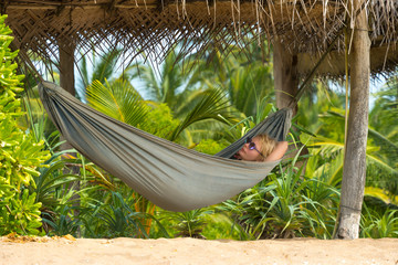 Young beautiful woman relaxing in hammock in a tropical resort.
