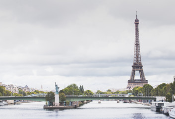 Eiffel Tower, Seine river and Statue of Liberty in Paris, France. Boats on Seine river.
