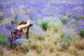 Young beautiful woman in blouse with flower ornament sitting at purple lavender field with camera in hands and taking picture.